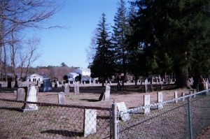 In of several rows of graves in an old cemetery, dry brown grass, chain link fence in the foreground, pines in the left background