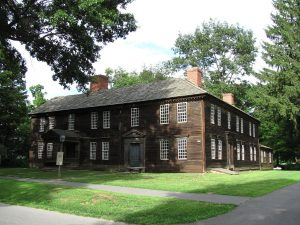 Historic 1795, two-story, brown sided building with two entrances, multiple brick chimneys, and mullioned windows. Building sits on a trim green lawn with paved paths up to the entrances.