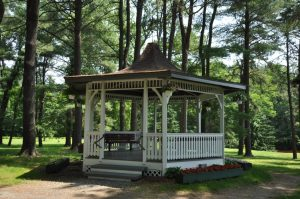 White gazebo with open sides and a pointed roof against a backdrop of lawn and pine trees. Flower boxes with red and white flowers surround the gazebo; hanging baskets with similar flowers hang from the points of the roof