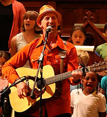 Musician Mister G wearing a hat and orange shirt, singing at a microphone, playing guitar. Children sing along in the background.