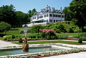 A large, white historic (1902) mansion stands in the background of a spring scene. A fountain sprays in the foreground of a formal flower garden in bloom.
