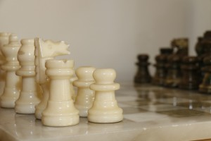 Chess board with pieces set up for beginning play. White pieces at the front; black pieces in the foreground.