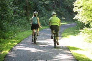 two bicyclists ride down a paved trail, lawn & woods on the sides. Both are wearing helmets.