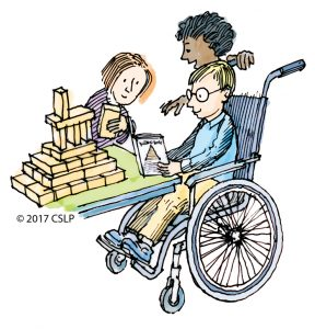 A white child, a black child, and a white child in a wheelchair wearing glasses build a structure with blocks. The child in the wheelchair consults a book.
